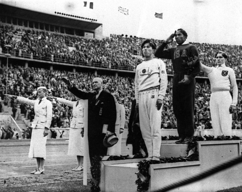 ADVANCE FOR WEEKEND AUG. 14-15--Olympic broad jump medalists salute during the medals ceremony Aug. 11, 1936 at the Summer Olympics in Berlin. From left on podium are: bronze medalist Jajima of Japan, gold medalist Jesse Owens of the United States and silver medalist Lutz Long of Germany. Long and German Olympic officials give the Nazi salute, while Owens gives a traditional salute. Owens was viewed as something of an oddity by the German crowds. Not only was he a brilliant sprinter, but he was the best long jumper in the world, as well. And, oh yes, there was one more thing.(AP Photo) ORG XMIT: NY177